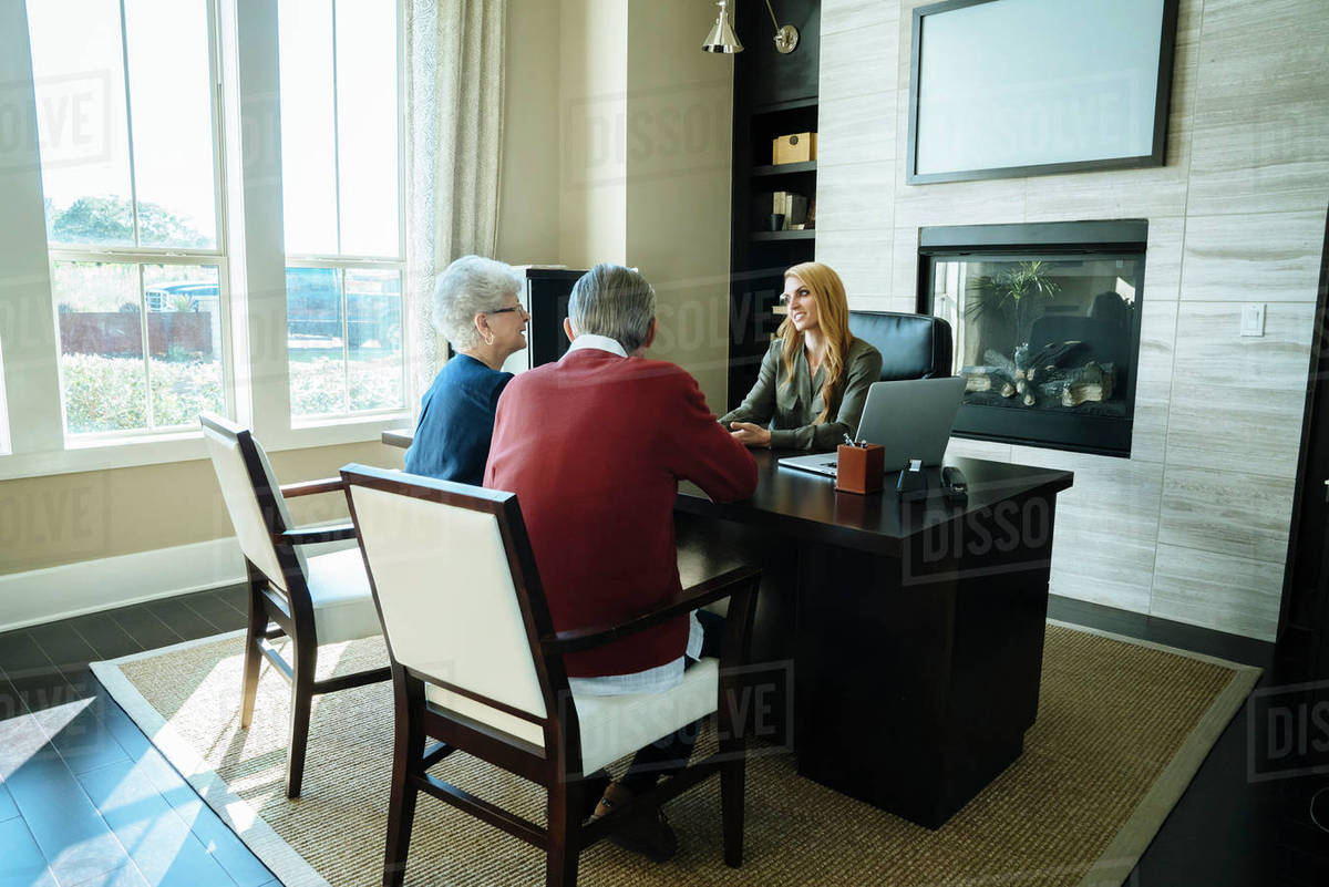 senior couple discussing with financial advisor while sitting in