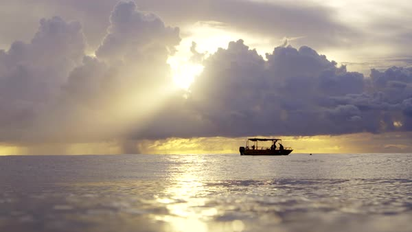 Lockdown shot of people in boat on sea against cloudy sky during sunset Royalty-free stock video