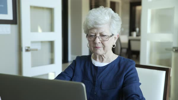 Handheld shot of senior woman using laptop computer at home Royalty-free stock video