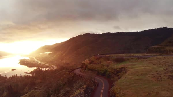 Drone point of road on mountain by river against cloudy sky during sunset Royalty-free stock video