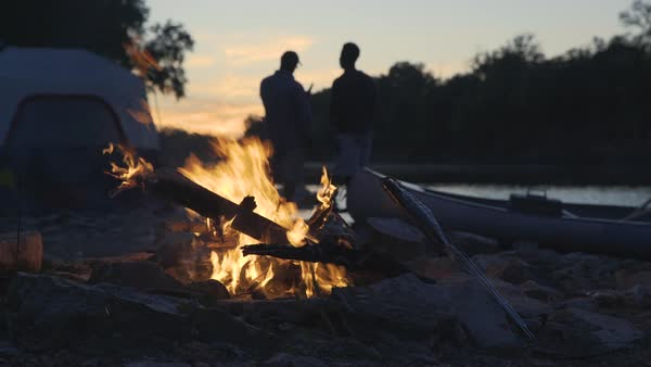 Dolly shot of burning campfire at lakeshore with father and son toasting beer bottles in background during sunset Royalty-free stock video
