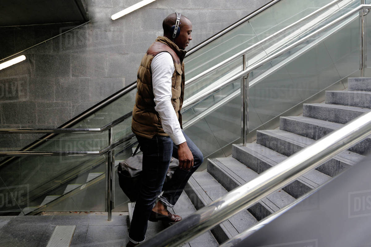 side view of man climbing steps at subway station stock photo