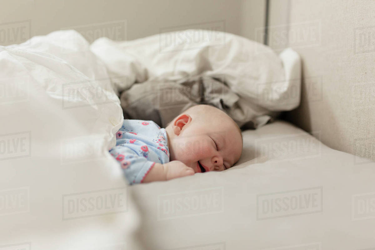 cute baby girl sleeping on bed at home - stock photo - dissolve