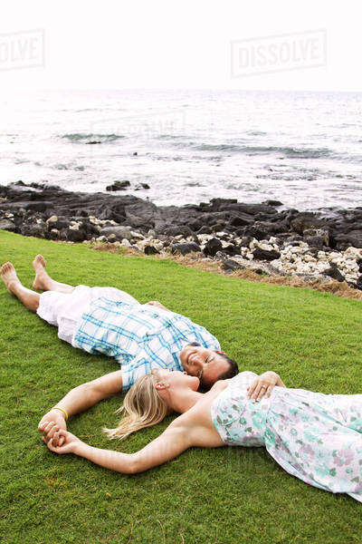Couple laying on grass near ocean Royalty-free stock photo