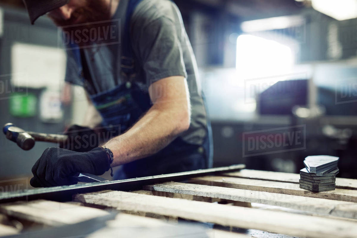 Midsection of blue collar worker using hammer and chisel in steel factory  stock photo