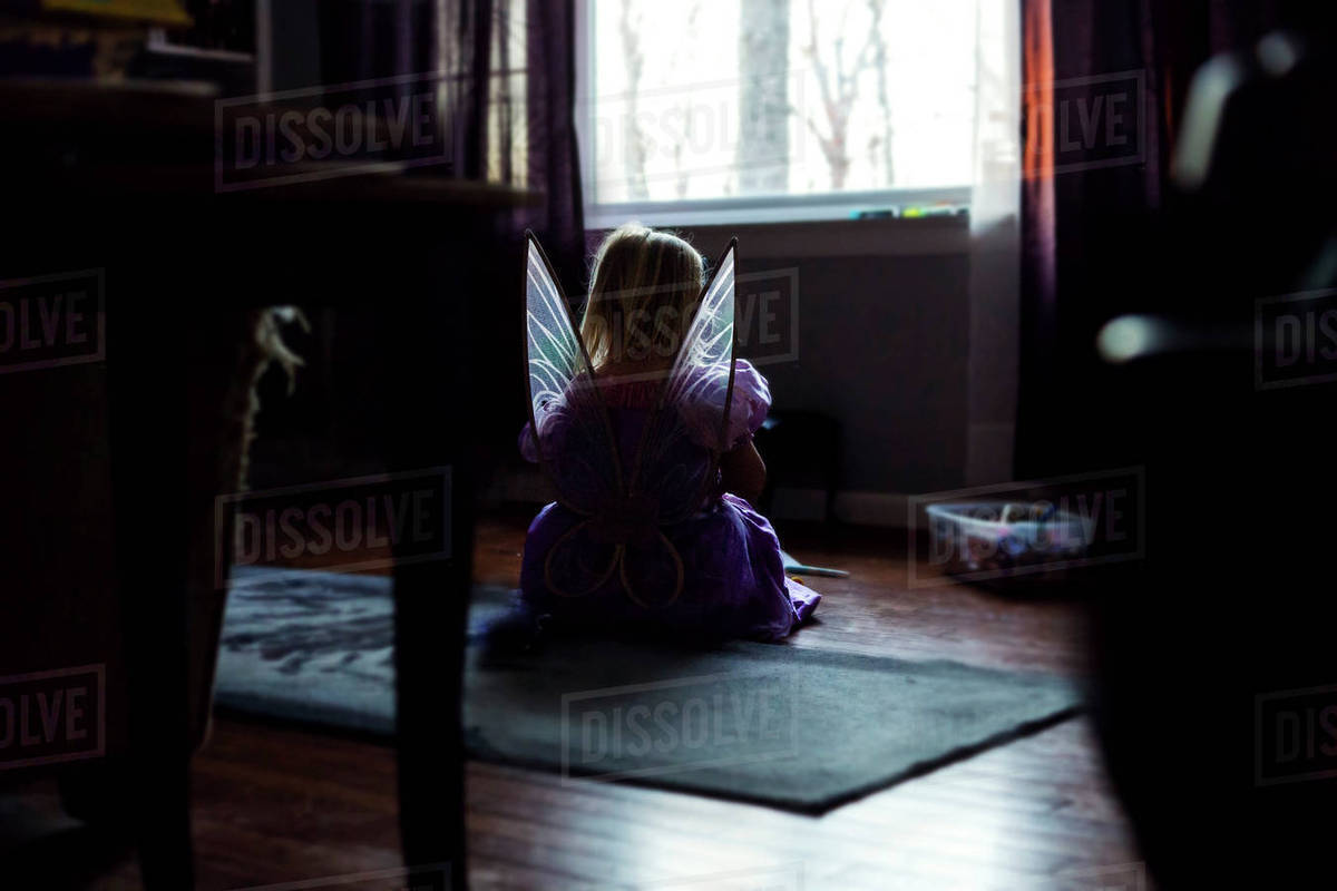 Rear view of girl in fairy costume sitting on floor at home Royalty-free stock photo
