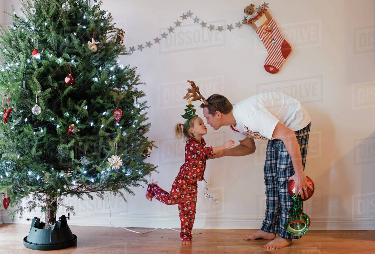 At Home Christmas Trees.Father Kissing Daughter While Standing By Christmas Tree At Home Stock Photo