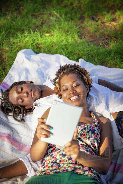 Young couple using tablet in park Royalty-free stock photo