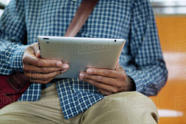 Young man sitting using digital tablet Royalty-free stock photo