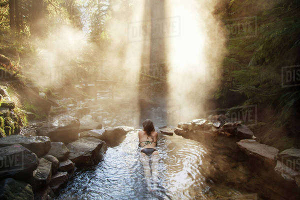 High angle view of woman relaxing in hot spring at forest Royalty-free stock photo