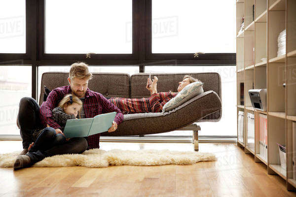 Father and daughter reading book by woman relaxing on sofa at home Royalty-free stock photo