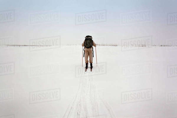 Rear view of man carrying backpack while skiing on snow covered field Royalty-free stock photo