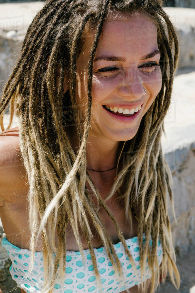 close up of cheerful young woman with dreadlocks stock photo