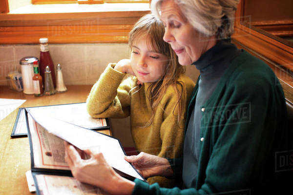 Grandmother with granddaughter (8-9) reading menu in restaurant Royalty-free stock photo
