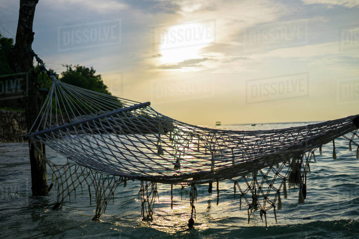 Empty hammock over sea against sky during sunset stock photo