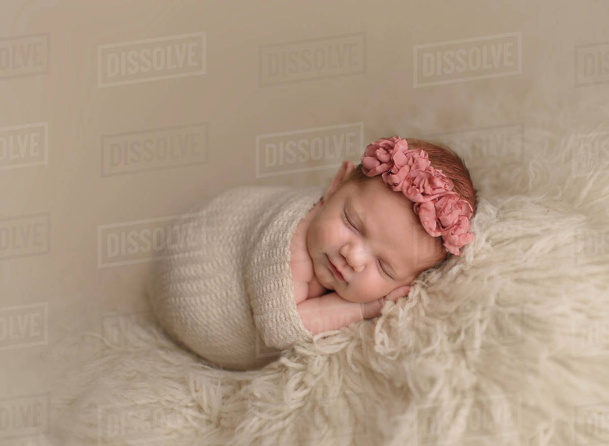 cute sleeping baby girl wrapped in blanket on rug at home - stock