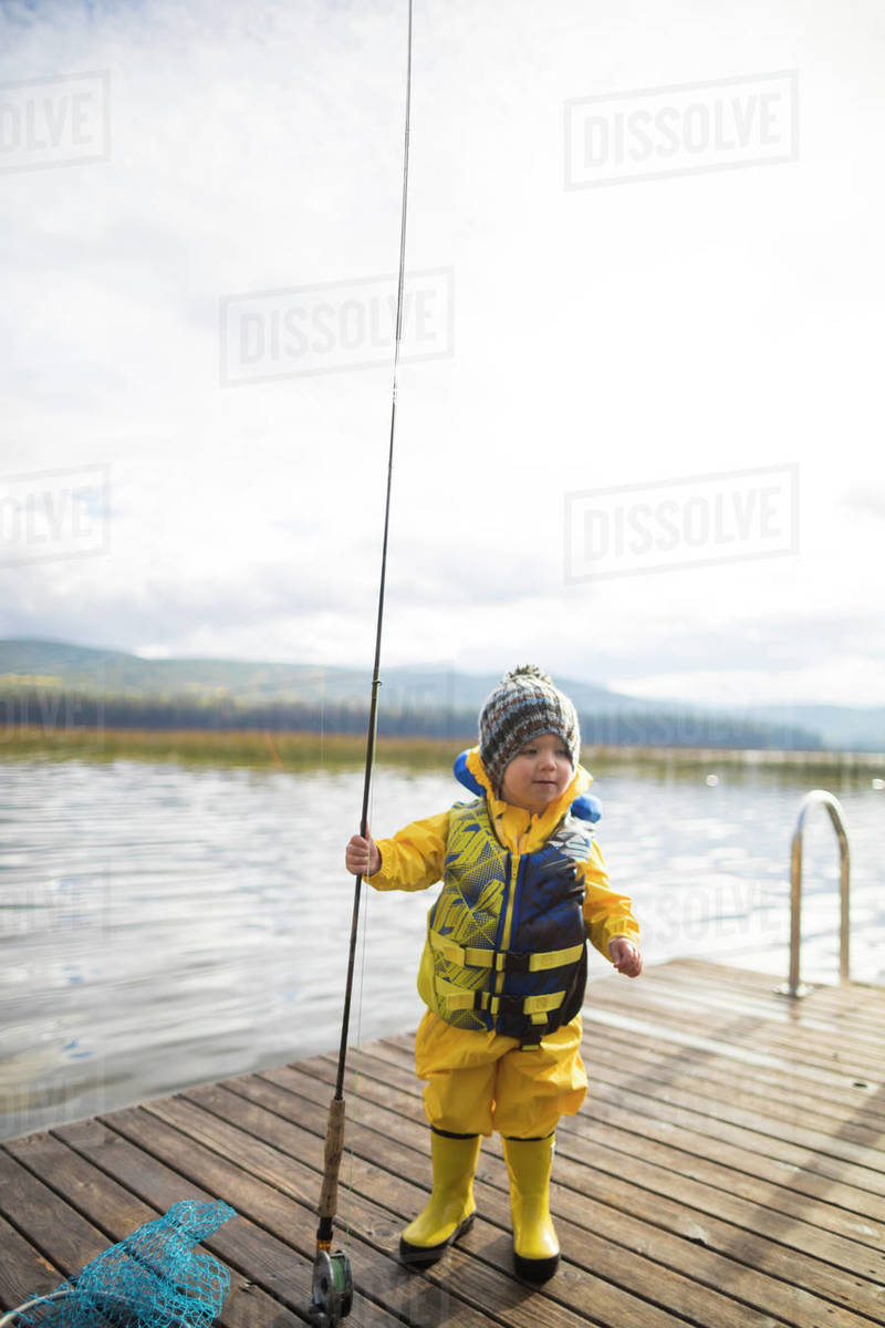 5ac027a1471f9 Baby boy wearing raincoat and life jacket while holding fishing rod on  wooden pier over lake stock photo