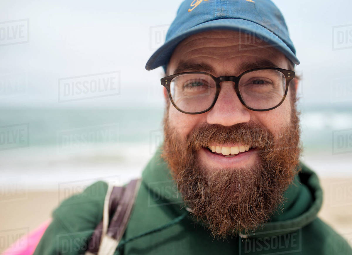Close-up portrait of smiling bearded man wearing cap and eyeglasses at beach 717eda35a17