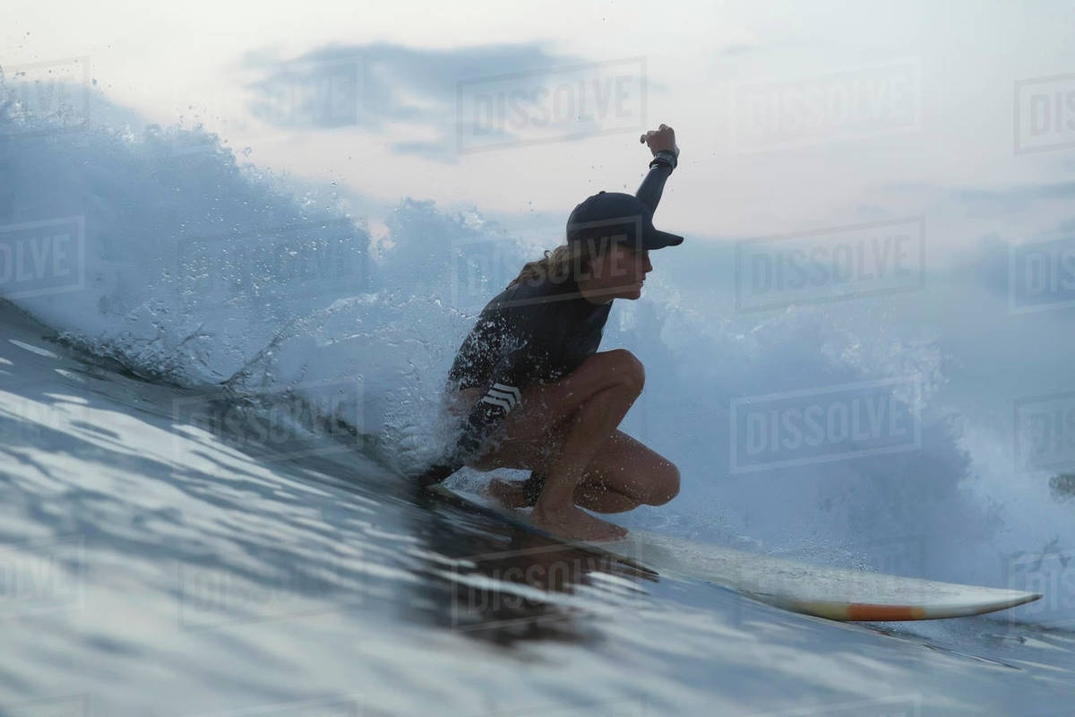 Woman Surfing On Sea Against Sky During Sunset Stock Photo