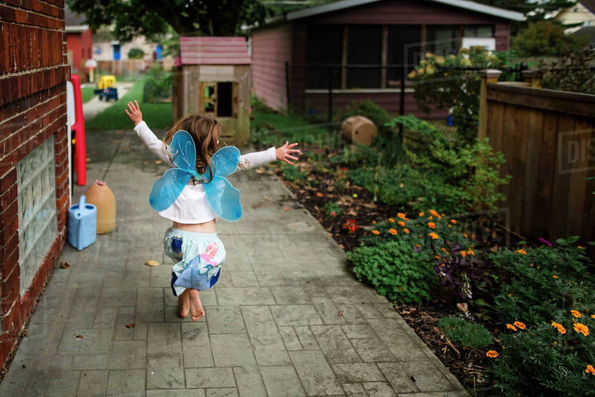Rear view of playful girl wearing costume wings while running at backyard Royalty-free stock photo