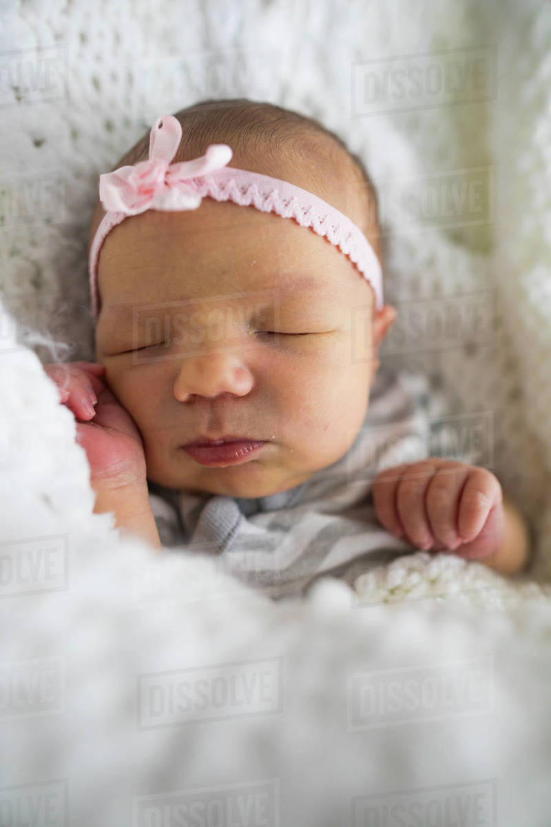 Close up of cute newborn baby girl wearing headband sleeping on bed at home
