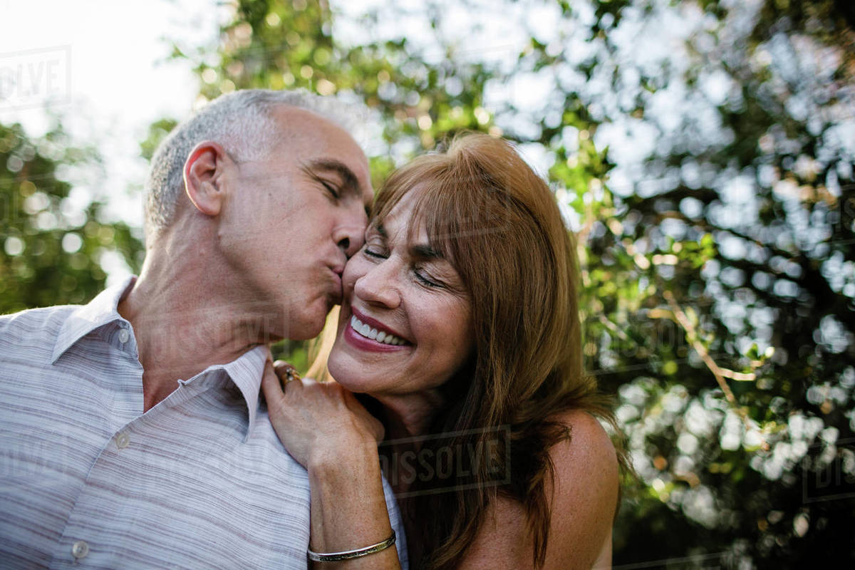 Low Angle View Of Romantic Husband Kissing Happy Wife Against Plants