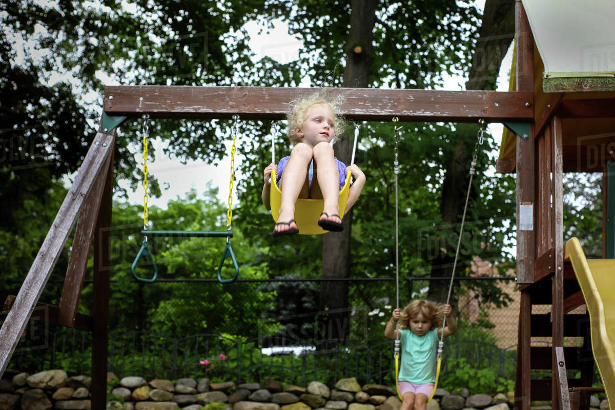 Cute Sisters Swinging On Swings Against Trees At Playground Stock Photo