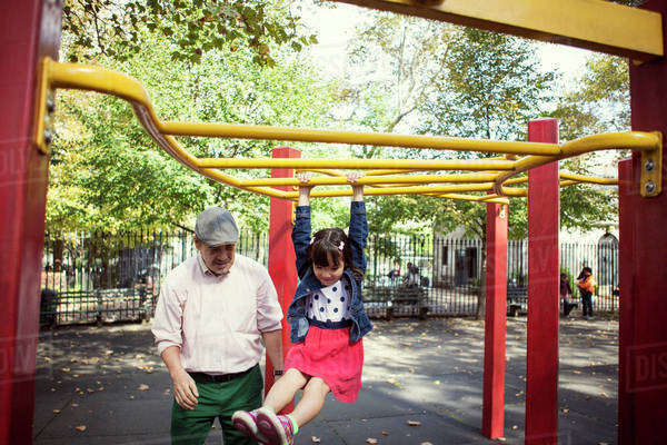 Grandfather and granddaughter (6-7) playing in playground Royalty-free stock photo
