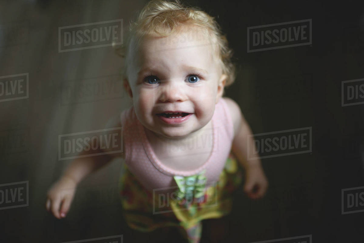 a52673e59011 High angle portrait of smiling cute baby girl standing on floor at ...