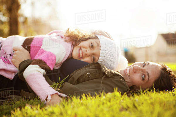 Mother lying in grass with daughter (6-7) Royalty-free stock photo