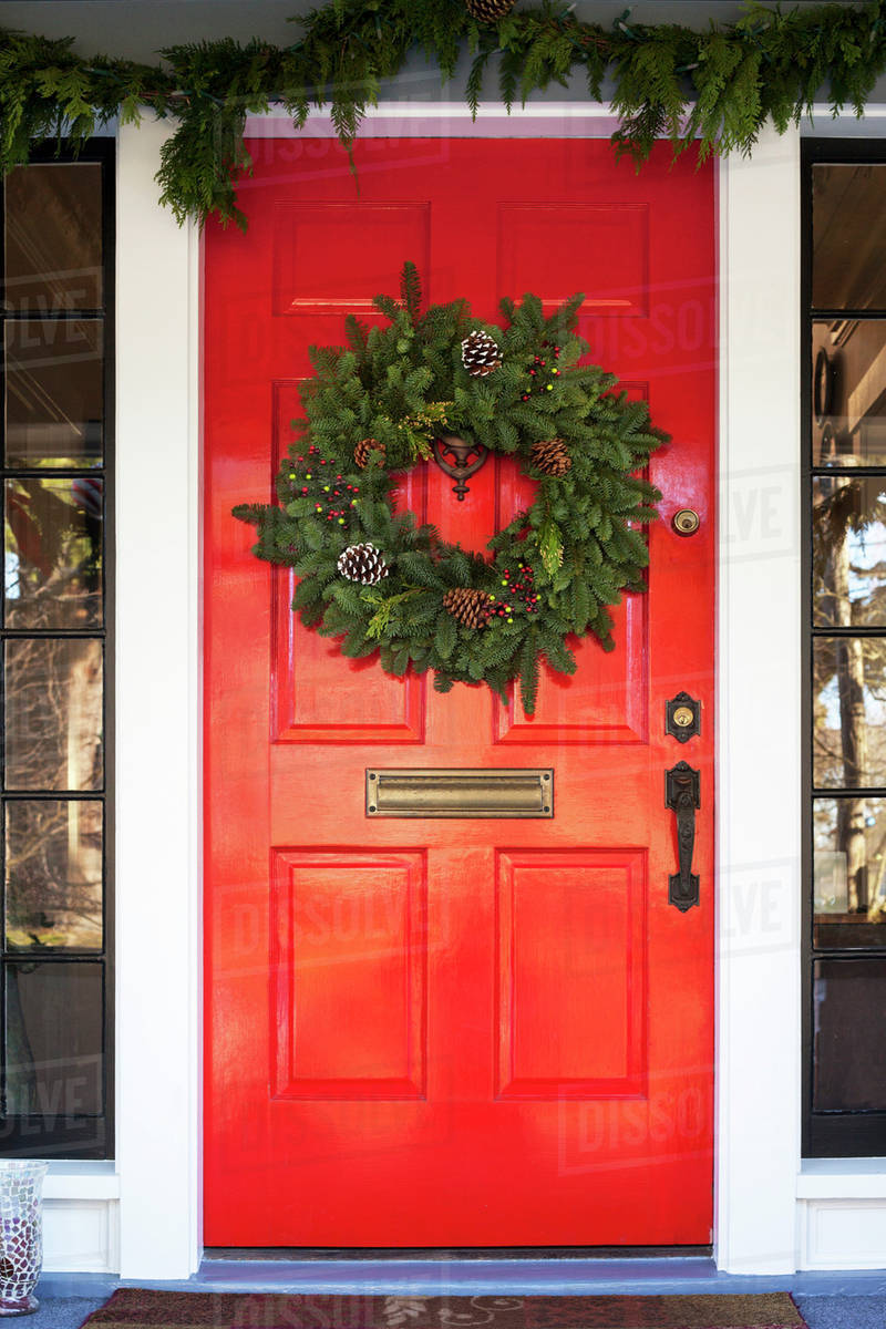 Close Up Shot Of Red Front Door With Christmas Wreath Stock Photo