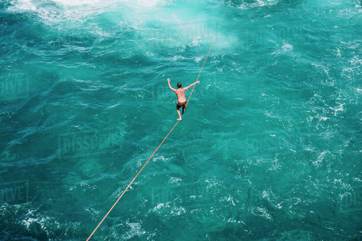 High angle view of carefree young man practicing slacklining over sea Royalty-free stock photo