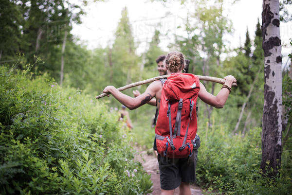 Couple hiking in forest female carrying backpack and wooden stick Royalty-free stock photo