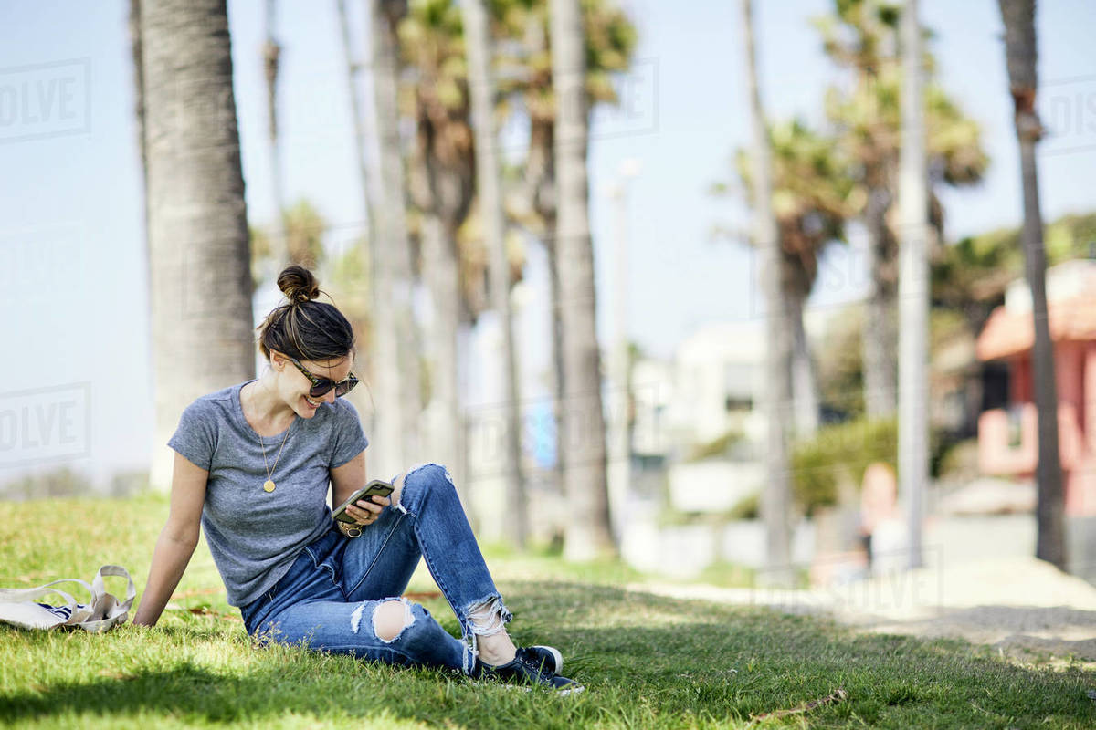 Smiling mid adult woman text messaging on smart phone while sitting on grass at beach Royalty-free stock photo