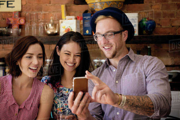 Man showing phone to female friends while standing at kitchen counter Royalty-free stock photo