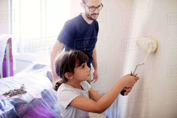 Father guiding daughter to paint wall in house Royalty-free stock photo