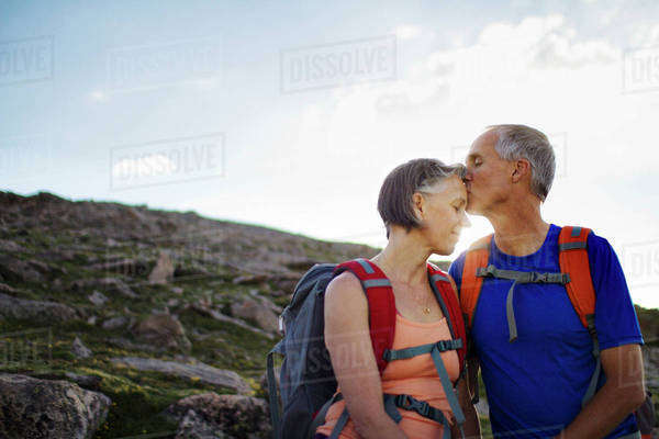 Mature couple kissing on mountain Royalty-free stock photo
