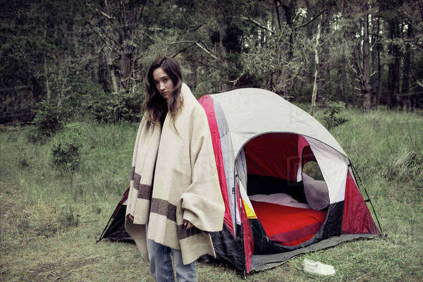 Woman wrapped in blanket standing outside tent against trees Royalty-free stock photo  sc 1 st  Dissolve & Woman standing at forest while being wrapped in blanket against ...