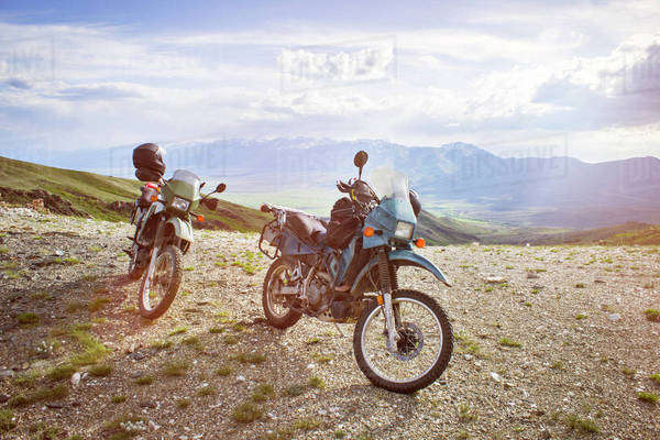 Motorcycles parked on field against mountains and sky Royalty-free stock photo