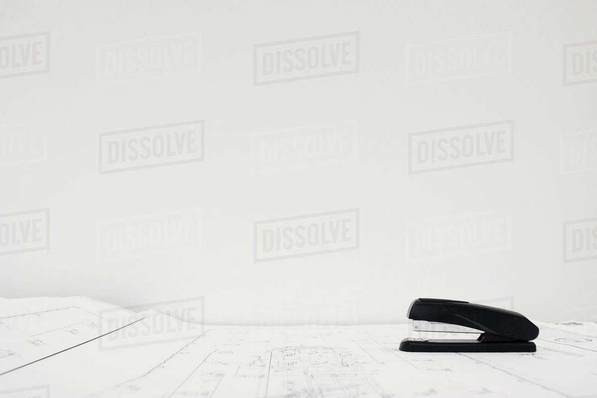 Stapler on blueprint against white background stock photo dissolve stapler on blueprint against white background malvernweather Choice Image