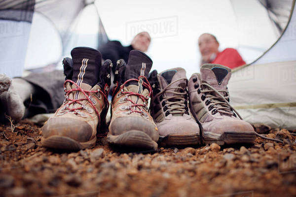 Close-up of dirty shoes with hikers relaxing in background Royalty-free stock photo