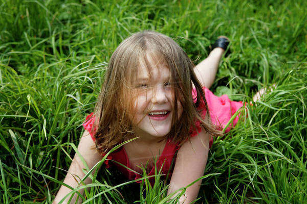 Young girl (6-7) laying in long grass Royalty-free stock photo