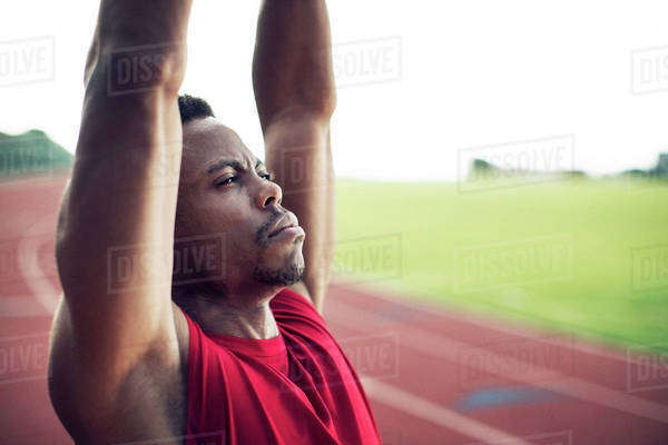 Close-up of sportsman with arms raised stretching on running track Royalty-free stock photo