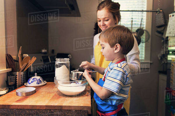 Little boy helping mother in kitchen Royalty-free stock photo
