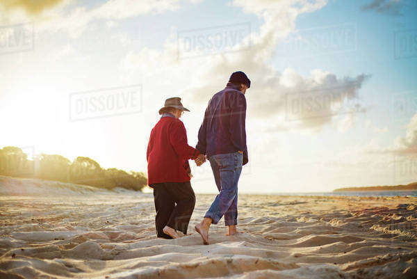 Senior couple holding hands while walking on sandy beach on sunny day Royalty-free stock photo