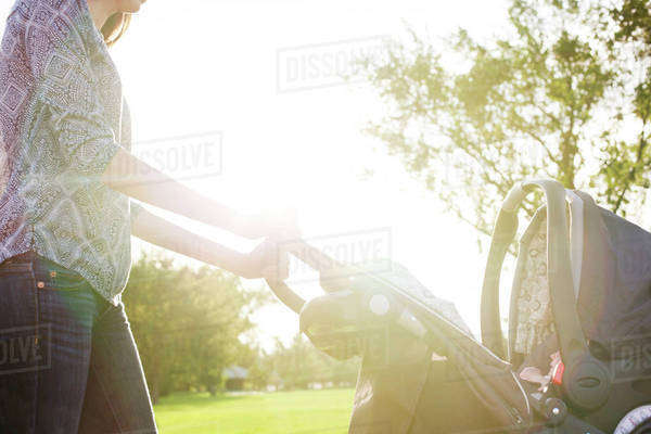 Midsection of woman walking with baby stroller on sunny day Royalty-free stock photo