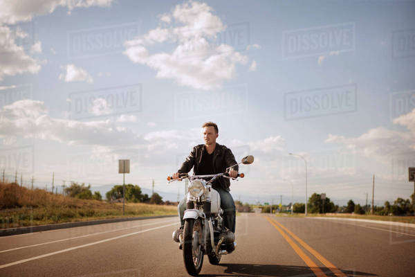 Young man riding motorcycle along country road Royalty-free stock photo