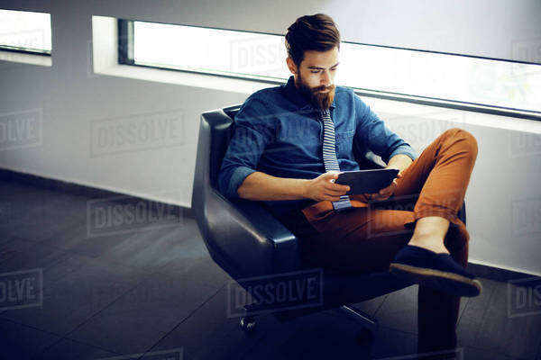 Young man with bear sitting in office and using digital tablet Royalty-free stock photo