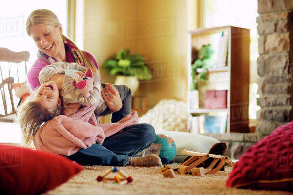 Mother with daughter sitting on floor in living room and laughing Royalty-free stock photo