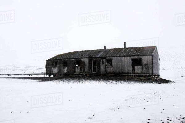 Abandoned house on snow covered field against sky at Deception Island Royalty-free stock photo